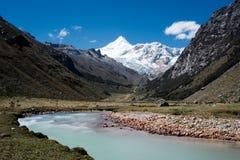 Bella valle della montagna con i picchi manifestazione-ricoperti e una torrente montano del turchese nella priorità alta Immagini Stock