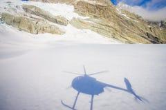 Bella vista alle montagne bianche coperte di neve, con un'ombra dell'elicottero nella neve, nel ` del sud s di Westland del sud Immagini Stock