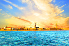 Bella vista chiesa di Riga del ` s del castello, di St Peter e la torre della cattedrale della cupola sulle banche del fiume di D fotografia stock libera da diritti