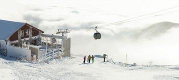 Bella vista dalla cima di un moutain con le cabine di funivia che superano sulle nuvole Fotografie Stock Libere da Diritti