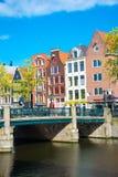 Bella vista dei canali di Amsterdam con il ponticello e le case olandesi tipiche Fotografia Stock Libera da Diritti