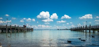 Bella vista del lago Chiemsee, con il pilastro di legno, il cielo nuvoloso blu e le anatre immagine stock