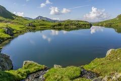 Bella vista del lago dell'alta montagna con il cielo rispecchiato in acqua Fotografia Stock Libera da Diritti