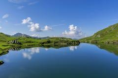 Bella vista del lago dell'alta montagna con il cielo rispecchiato in acqua Immagini Stock
