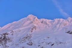 Bella vista del picco di montagna con la luce di tramonto sulla cima contro Immagini Stock Libere da Diritti