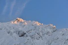 Bella vista del picco di montagna con la luce di tramonto sulla cima contro Fotografia Stock