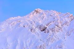 Bella vista del picco di montagna con la luce di tramonto sulla cima contro Immagine Stock Libera da Diritti