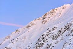 Bella vista del picco di montagna con la luce di tramonto sulla cima contro Fotografie Stock Libere da Diritti