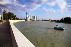 Bella vista dell'architettura della città uguagliante, del fiume e della barca di galleggiamento fotografie stock libere da diritti
