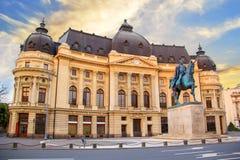 Bella vista della costruzione della biblioteca universitaria centrale con il monumento equestre a re Karol I a Bucarest, Romania fotografia stock libera da diritti