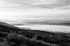 Bella vista della valle dell'Umbria in una mattina di inverno, con gli alberi della copertura della nebbia e case e piante verde  Immagini Stock