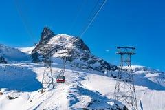 Bella vista delle alpi coperte di neve e di cabina di funivia rossa al mA Fotografia Stock Libera da Diritti