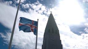 Bella vista di bella chiesa Hallgrimskirkja Reykjavik, in Islanda e bandiera nazionale ondeggianti sul vento Immagini Stock