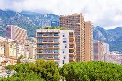 Bella vista di luce del giorno alle costruzioni alte della città, agli alberi verdi e Fotografia Stock Libera da Diritti