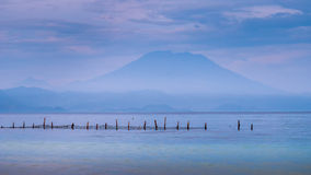 Bella vista di sera alla st Agung Vulcano su Bali dall'isola di Nusa Penida, rete nella parte anteriore alcune nuvole nel fondo Immagine Stock