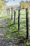 Bella vista di un sentiero per pedoni recintato con i pali ed il filo spinato di legno fotografie stock
