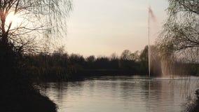 Bella vista di una fontana in un parco pubblico al tramonto in lampadina video d archivio