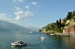 Bella vista panoramica al lago Como al fronte lago di Varenna con la gente che si siede in una barca a vela immagini stock