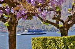 Bella vista panoramica al traghetto che passa il lago Como a Bellagio nel giorno soleggiato della molla in anticipo fotografia stock