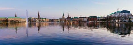 Bella vista panoramica del municipio del fiume di Alster e di Amburgo - Rathaus alla sera dei guadagni della molla durante l'ora  Fotografia Stock