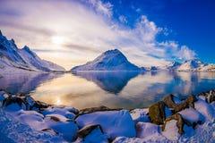Bella vista scenica splendida della montagna che riflette nel lago in Svolvaer, con le rocce coperte di neve Immagine Stock