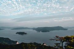Bella vista sugli alberi e sulle aziende agricole della perla e del cielo nuvoloso dal supporto Misen all'isola di Miyajima a Hir immagini stock