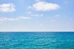 Bella vista sul mare con la navigazione bianca dell'yacht immagini stock libere da diritti