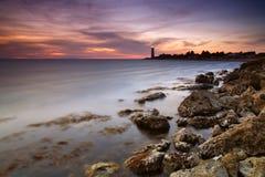 Bella vista sul mare con un faro al tramonto Immagine Stock