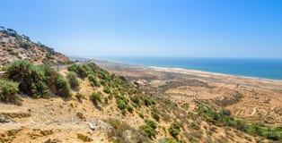 Bella vista sulla spiaggia oceanica dall'alta collina nel Marocco La serpentina della strada va verso l'oceano Colpo di panorama Immagine Stock Libera da Diritti