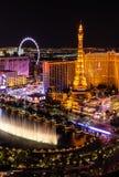 Bellagio Fonteinen tegenover Parijs Las Vegas bij nacht stock foto's