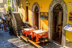 Outdoor cozy street restaurant in old Bellagio. BELLAGIO, ITALY - AUGUST 03, 2015: Outdoor cozy street restaurant in old Bellagio, Como lake, Italy Stock Photo