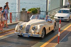 Happy man drives out his vintage beige Jaguar XK120, a sports car manufactured by Jaguar circa 1950, from the ferry boat royalty free stock photo