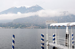 Bellagio Water Taxis. Bellagio water taxi pier and winter view of Lago Como. Blue mood Royalty Free Stock Images