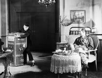Bellboy που αγωνίζεται με τον κορμό στο δωμάτιο φιλοξενουμένων (όλα τα πρόσωπα που απεικονίζονται δεν ζουν περισσότερο και κανένα Στοκ Εικόνες