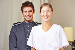 Bellboy and hotel maid in room. Portrait of bellboy and hotel maid in a hotel room Royalty Free Stock Photography