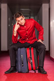 Bellboy with Luggages. Tired Bellboy with Luggages in the Hotel Royalty Free Stock Photography