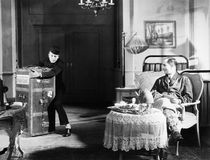 Bellboy struggling with trunk in guests room. (All persons depicted are no longer living and no estate exists. Supplier grants that there will be no model stock photo