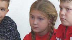 Belle écolière avec des tresses au bureau à côté du garçon dans la salle de classe banque de vidéos