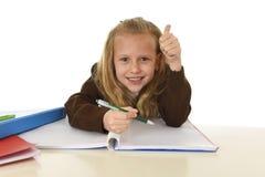 Belle écolière dans l'uniforme scolaire avec la séance heureuse de sourire de cheveux blonds sur le bureau faisant des devoirs images libres de droits