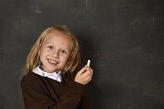 Belle écolière douce blonde dans l'uniforme jugeant l'écriture de craie sur le sourire de tableau noir heureuse Images libres de droits