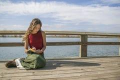 Belle écriture aux cheveux longs de femme en journal près de lac rural Image stock