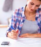 Belle écriture de jeune femme quelque chose dans son bloc-notes Photos stock