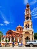 Belle église grecque orange sur l'île de Rhodes Le ciel lumineux avec des nuages Photos stock