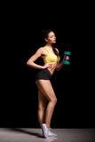 Belle élaboration sportive de femme Exercice de poids avec l'haltère sur le fond noir Photographie stock