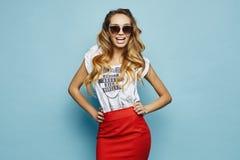 Belle, émotive et à la mode fille modèle blonde dans le T-shirt blanc, dans la jupe rouge et des lunettes de soleil élégantes sou photo libre de droits