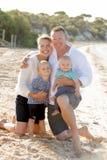 Belle épouse et mari de famille tenant la petits fille et bébé garçon sur la plage Photos stock