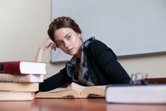 Belle étudiante à une table avec des livres Image libre de droits