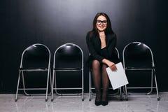 Belle étudiante attirante de costume tenant le dossier de réunion se reposant sur la chaise et regardant le travail de pensée de  image stock