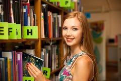 Belle étudiante de jeune femme dans la bibliothèque Photo stock