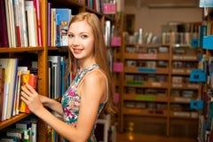 Belle étudiante de jeune femme dans la bibliothèque Images libres de droits